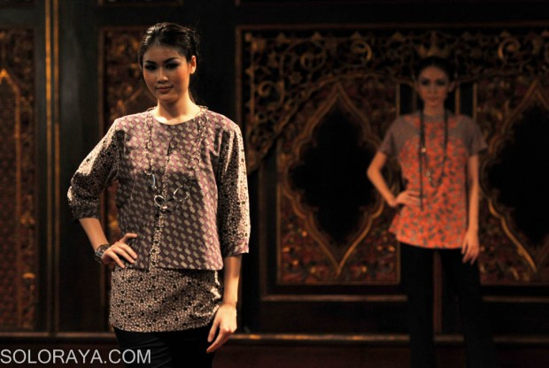 Model mengenakan pakaian batik gaya modern pada peragaan busana batik ...