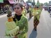 Peserta Kirab Sendang Ledhek Kadipiro membawa sesaji kecil berisi buah-buahan saat melintas di jalan utama kawasan Kadipiro Solo.