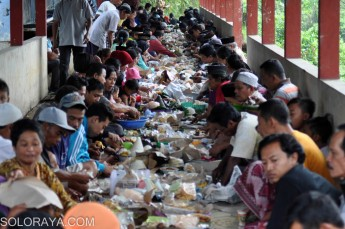 Sejumlah warga makan bersama saat tradisi saparan di pemakaman umum Nyamplung, Ampel, Boyolali, Jawa Tengah, Jumat (19/12). Setiap bulan Sapar penanggalan jawa, warga setempat melakukan bersih makam, berdoa serta makan bersama di area pemakaman itu. ANTARA FOTO/Aloysius Jarot Nugroho/Rei/Spt/14.