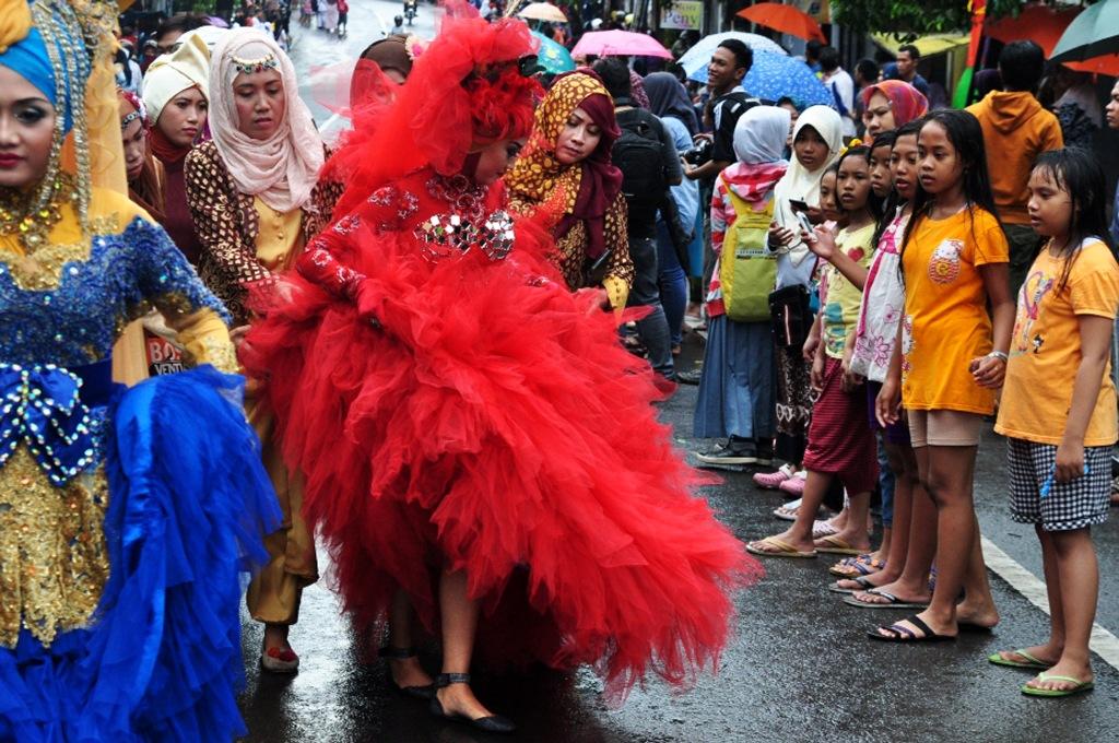 Sejumlah warga menyaksikan kirab budaya di Gresik, Jawa Timur, Senin (9/3). Kirab budaya tersebut untuk memperingati Hari Jadi ke 528 Kota Gresik. .ANTARA FOTO/Abdul Malik Ibrahim/